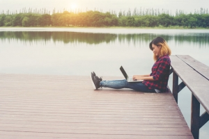 girl sitting on small bridge with laptop